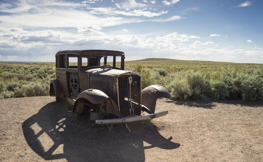brown vintage car on brown dirt road during daytime