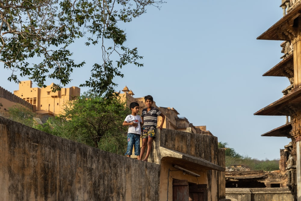 man and woman standing on concrete wall during daytime