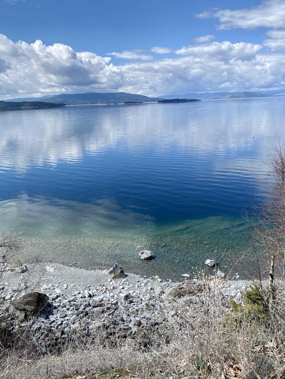 blue calm water near gray rocks during daytime