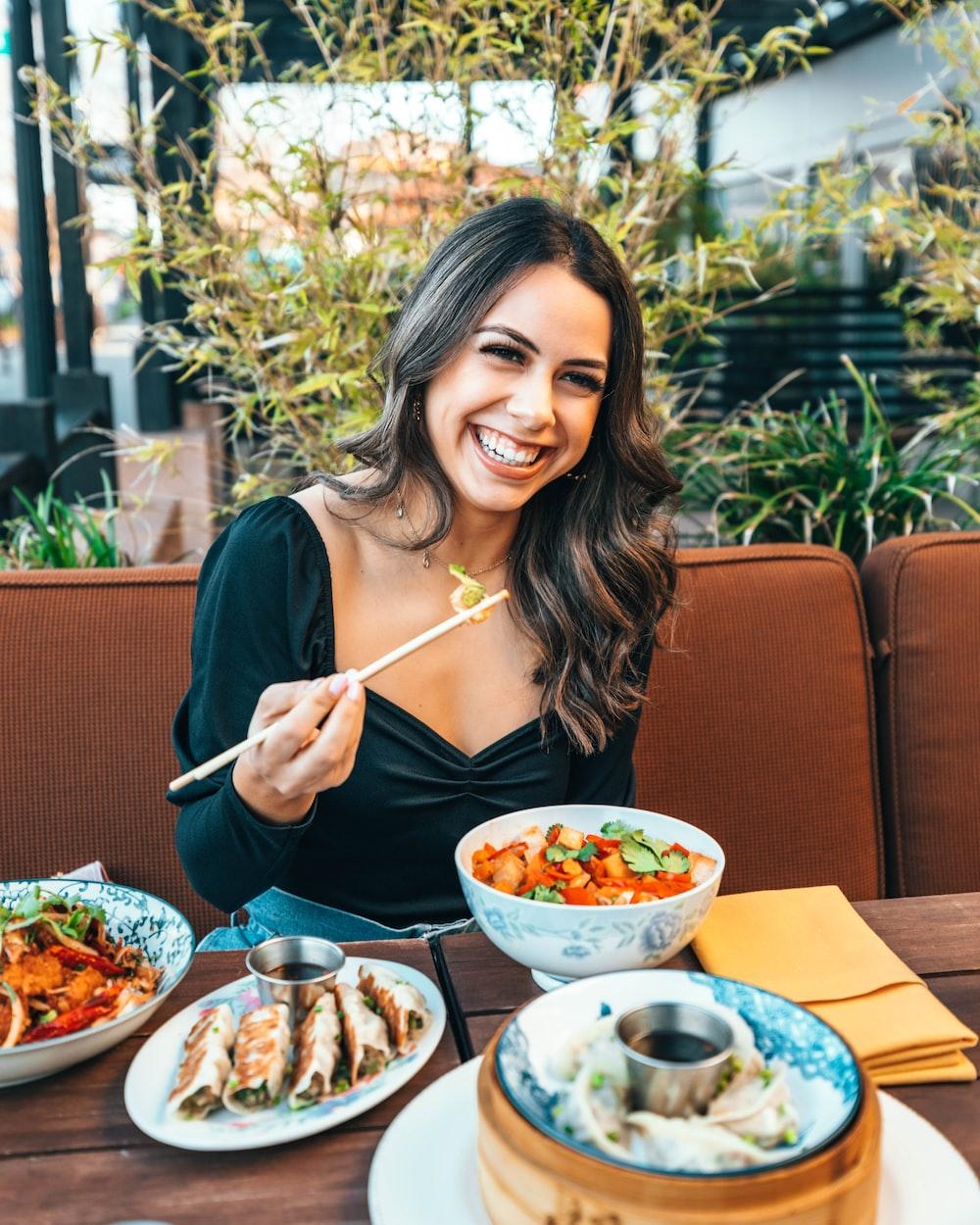 woman in blue long sleeve shirt holding chopsticks