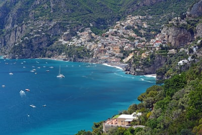 aerial view of body of water near green trees and houses during daytime amalfi coast teams background