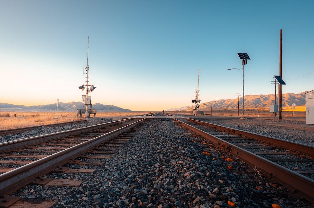train rail tracks under blue sky during daytime