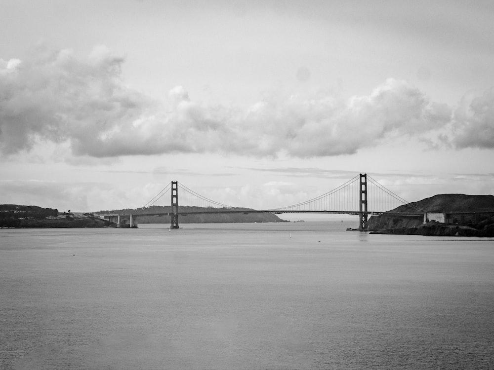 grayscale photo of bridge under cloudy sky