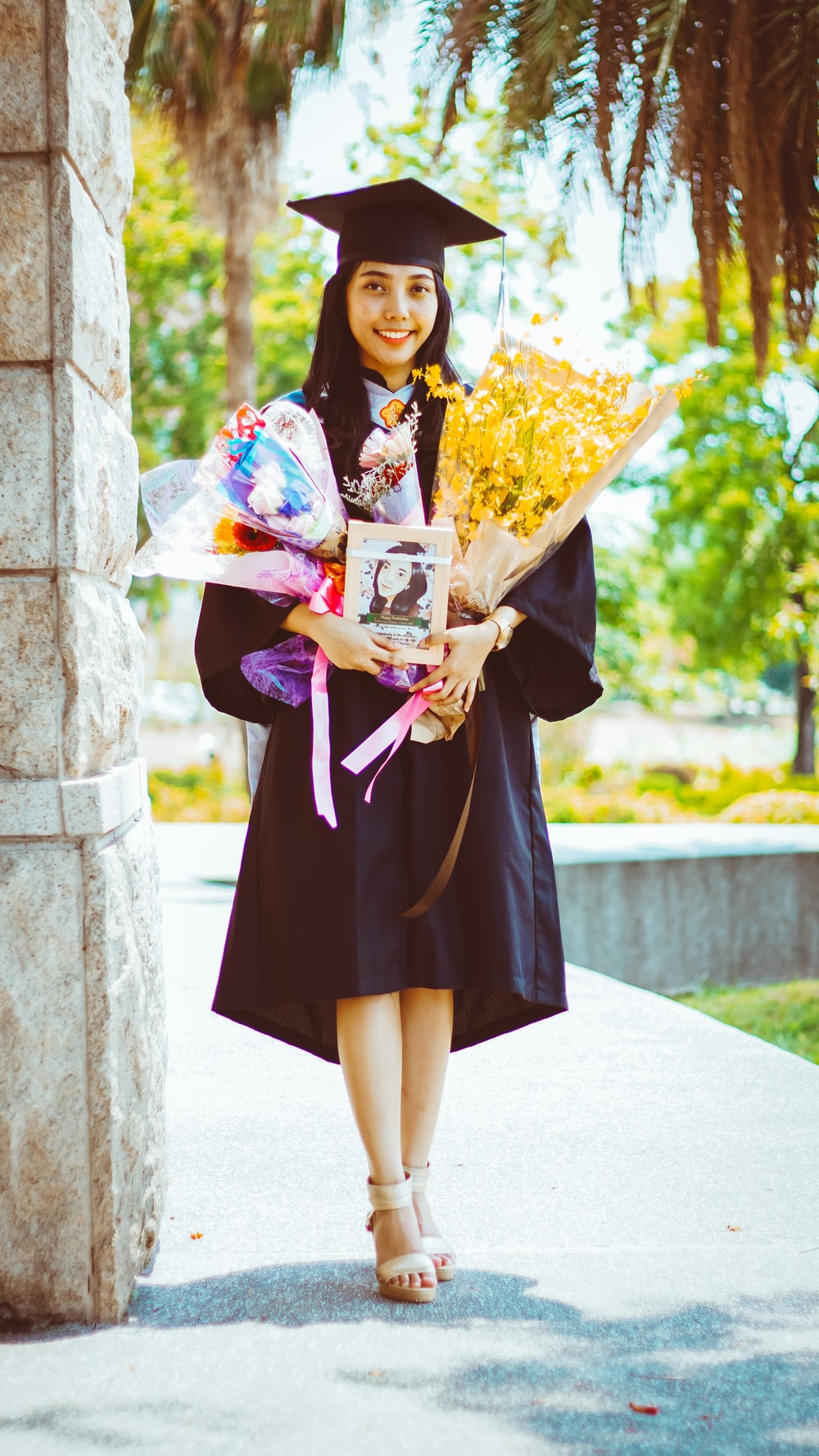 woman in black and purple academic dress holding bouquet of flowers
