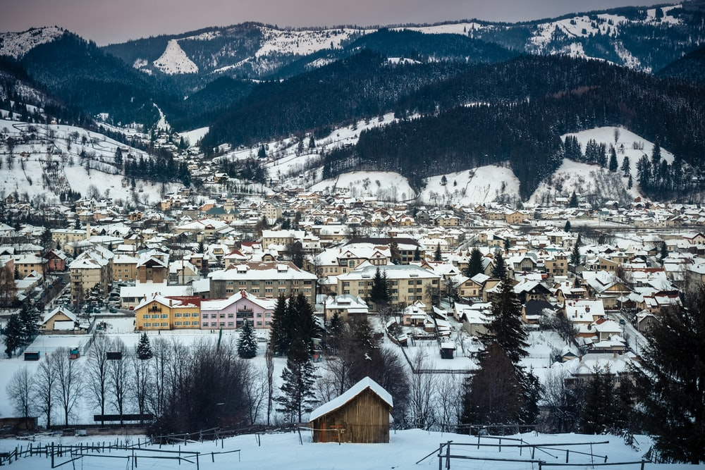 brown and white houses near snow covered mountain during daytime