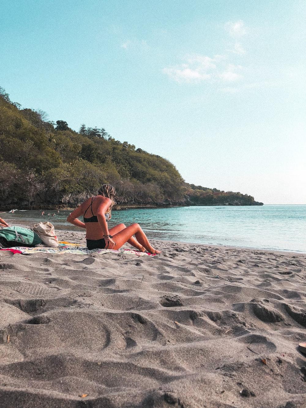 woman in bikini lying on beach sand during daytime