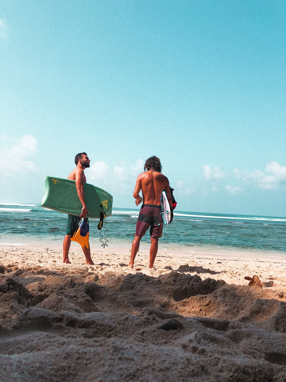 2 men and 2 women running on beach during daytime