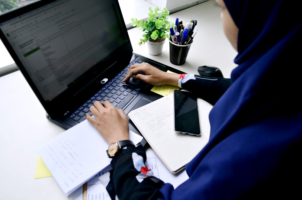 person in blue long sleeve shirt using black laptop computer