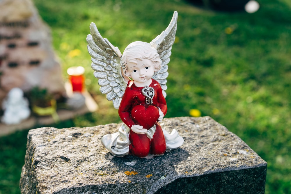 white angel figurine on gray concrete surface