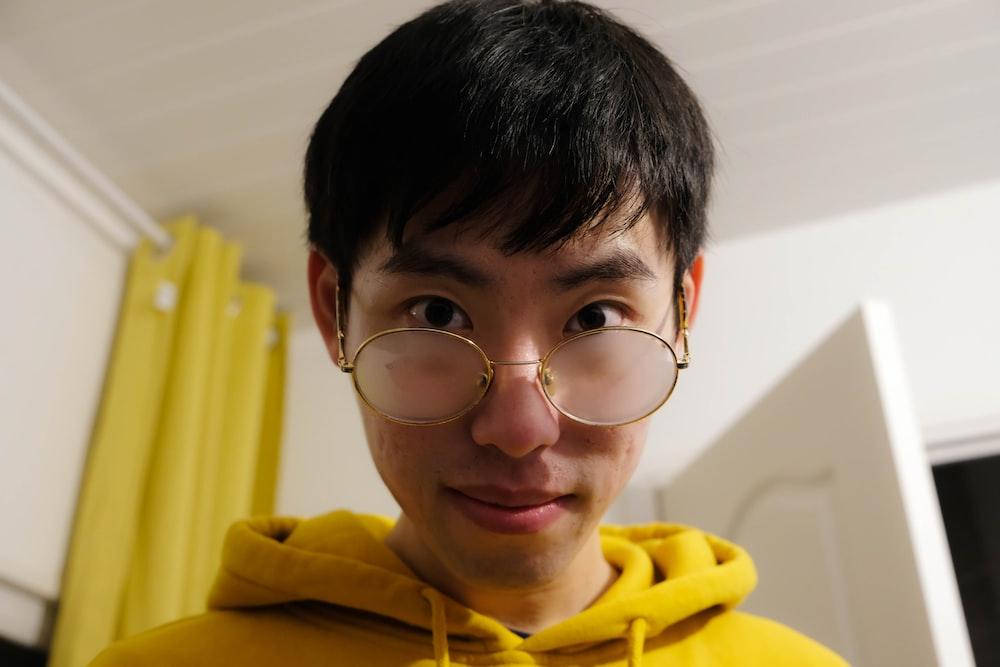boy in yellow hoodie wearing eyeglasses