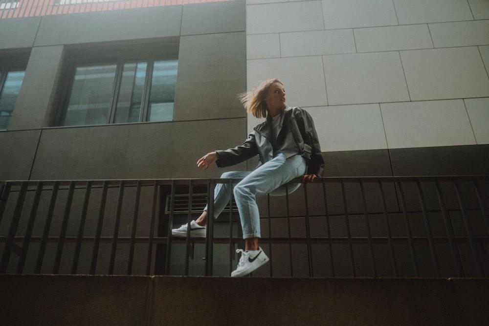woman in black jacket and blue denim jeans sitting on black metal railings