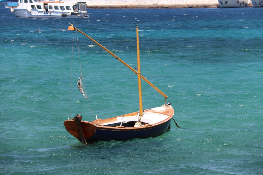 brown and white boat on sea during daytime