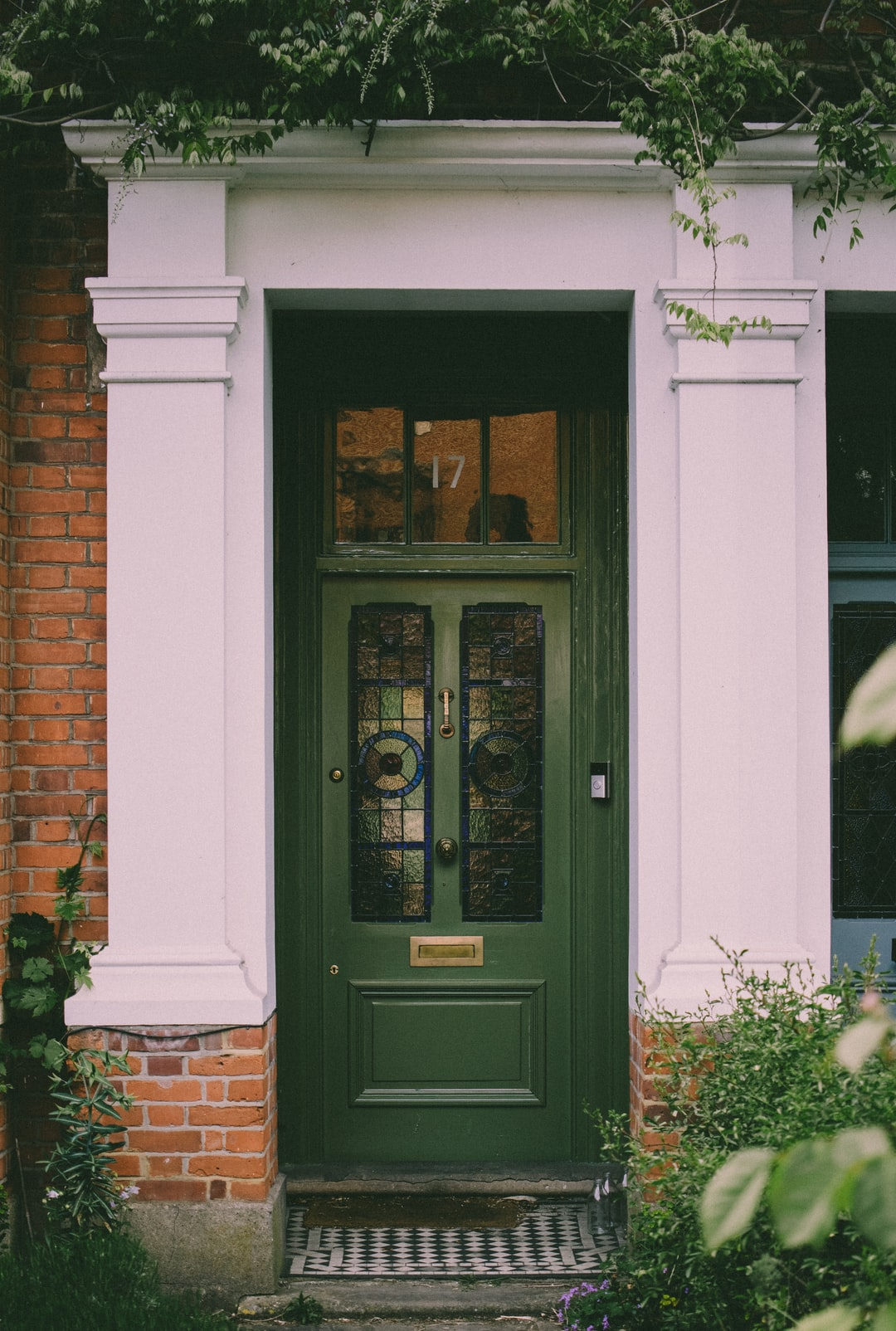 Green door, surrounded by plants.