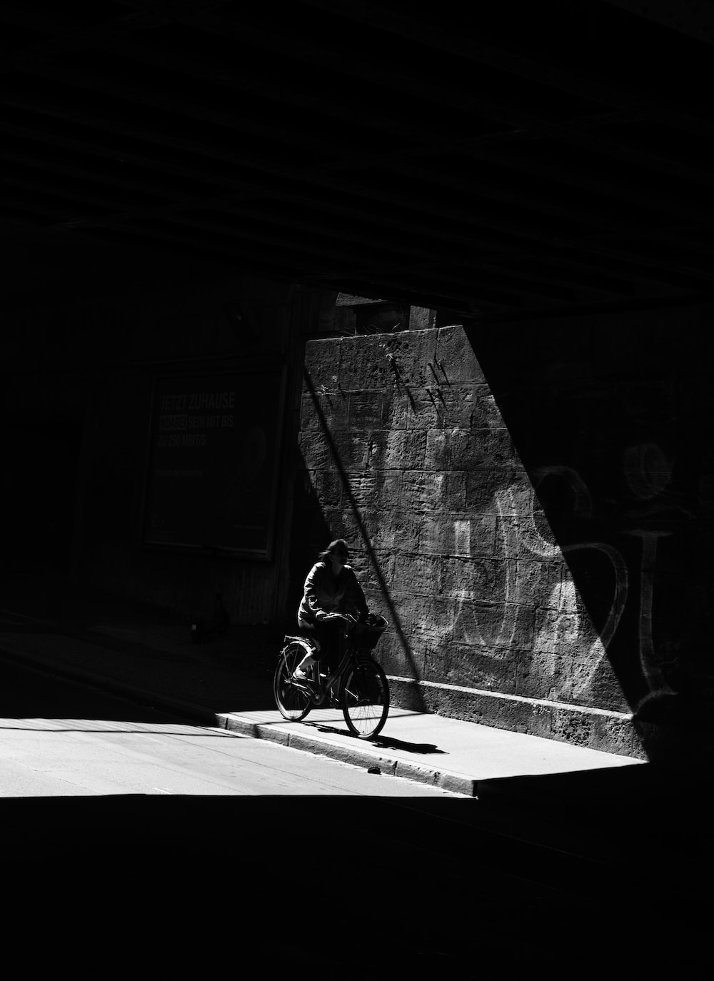 grayscale photo of person riding bicycle