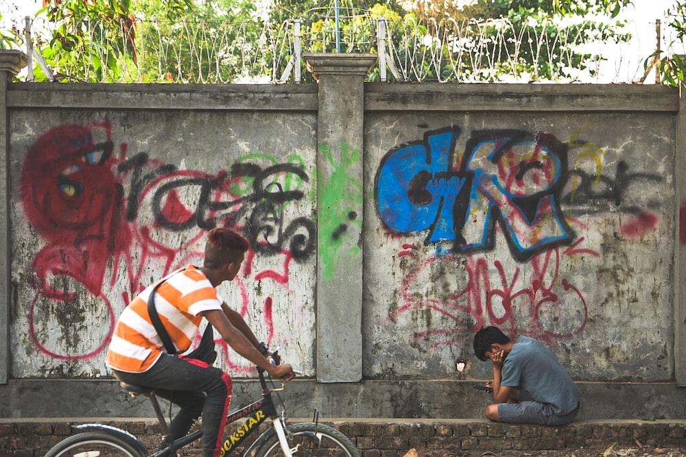 man in white and orange stripe shirt riding on black bicycle