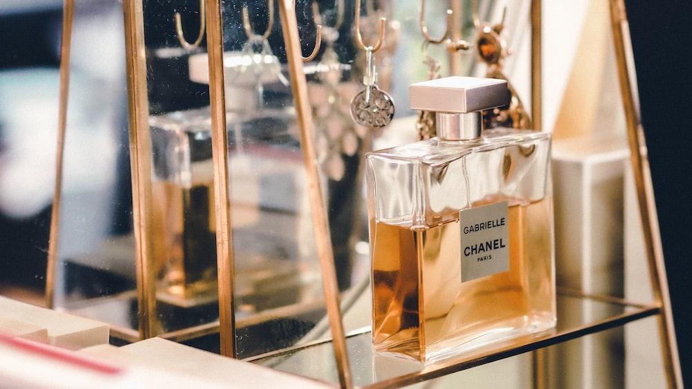 clear glass perfume bottle on glass shelf
