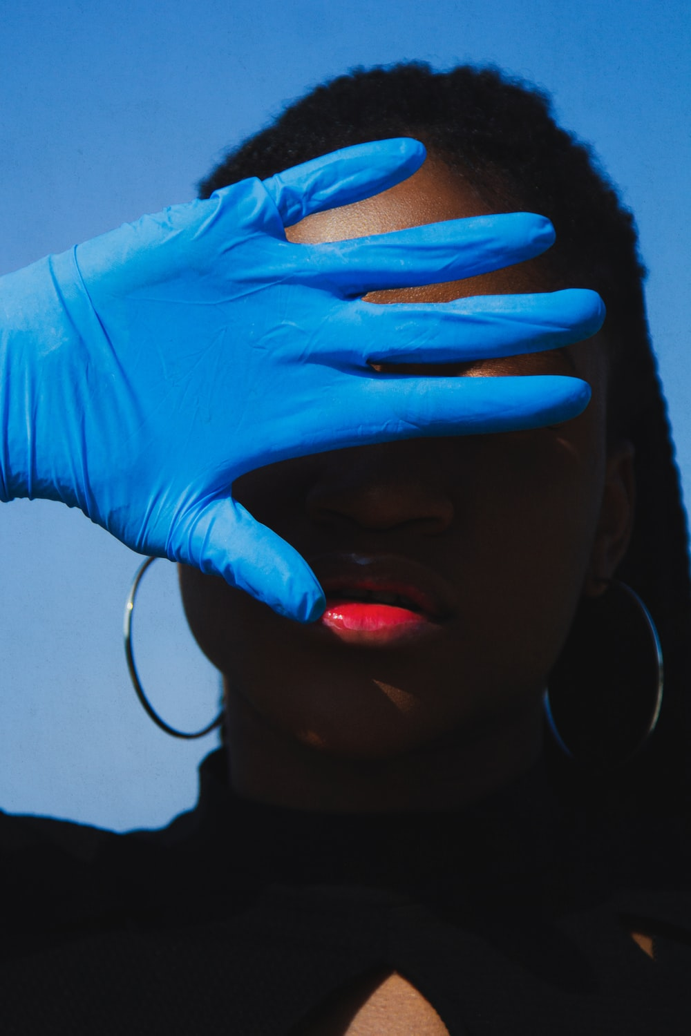 Woman partially hiding her face wearing a blue medical latex glove