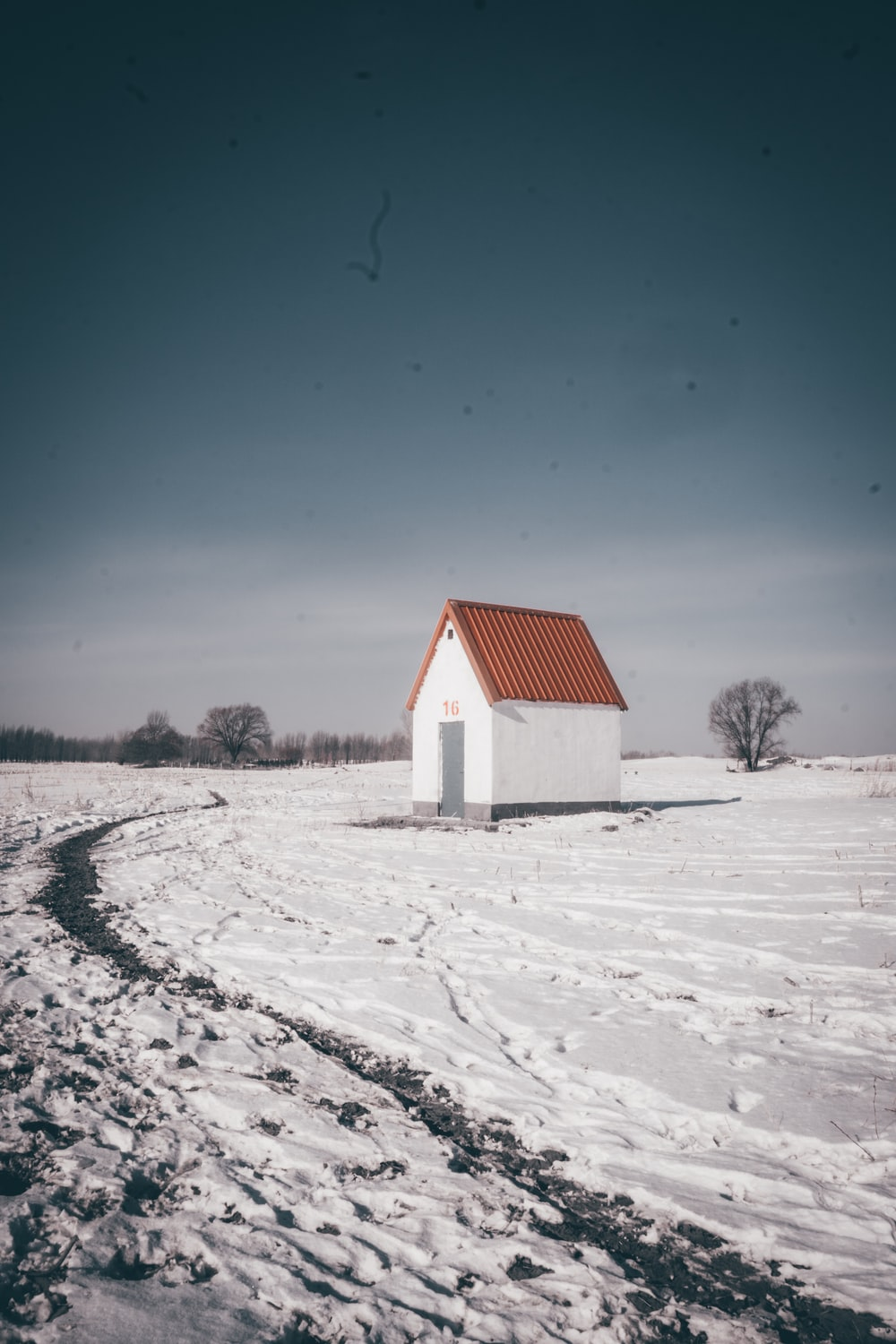 white and red house on snow covered ground