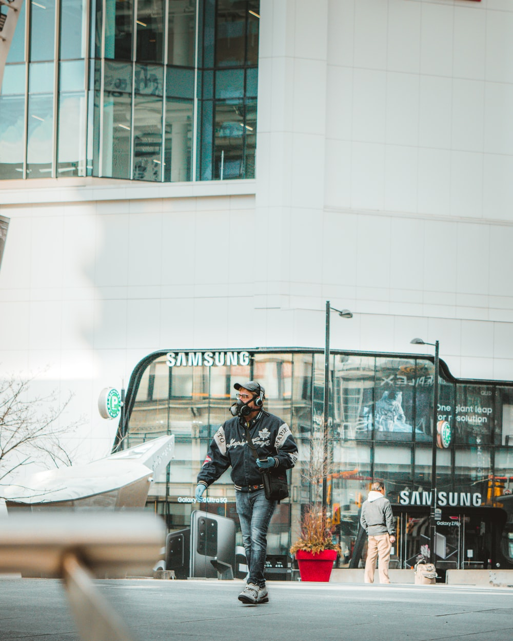 man in black jacket and black pants sitting on black steel bench during daytime