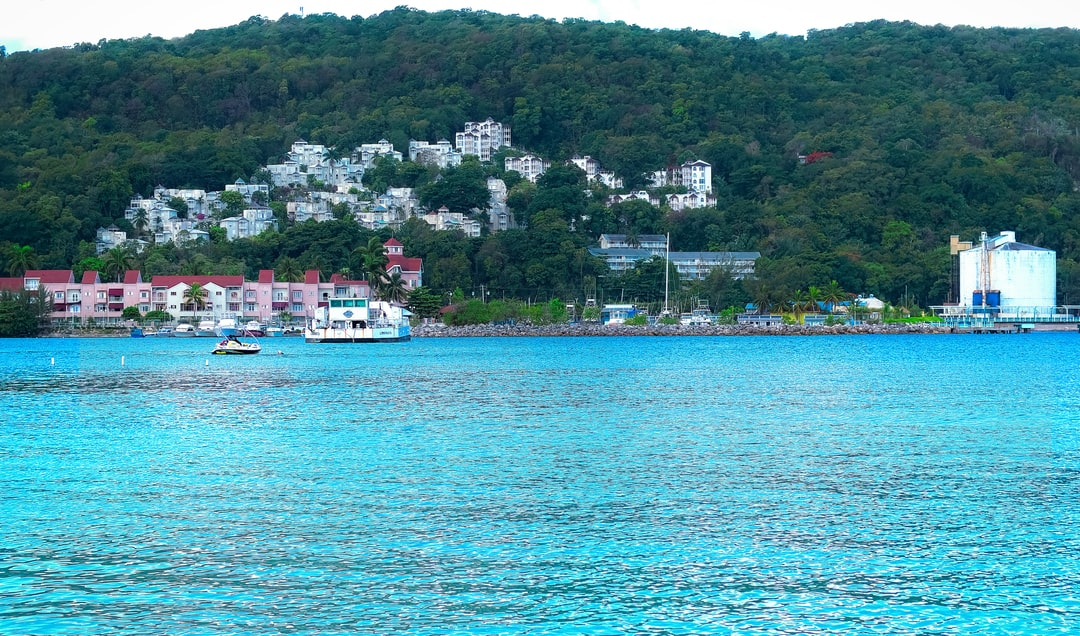 The view from across The Moon Palace Resort Beach in Ochos Rios Jamaica features a mountainside, homes and apartments, as well as a water treatment facility.