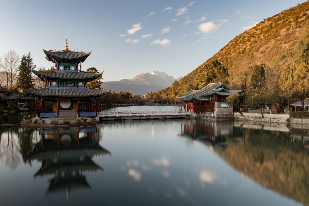 brown and green pagoda on body of water near mountain under blue sky during daytime