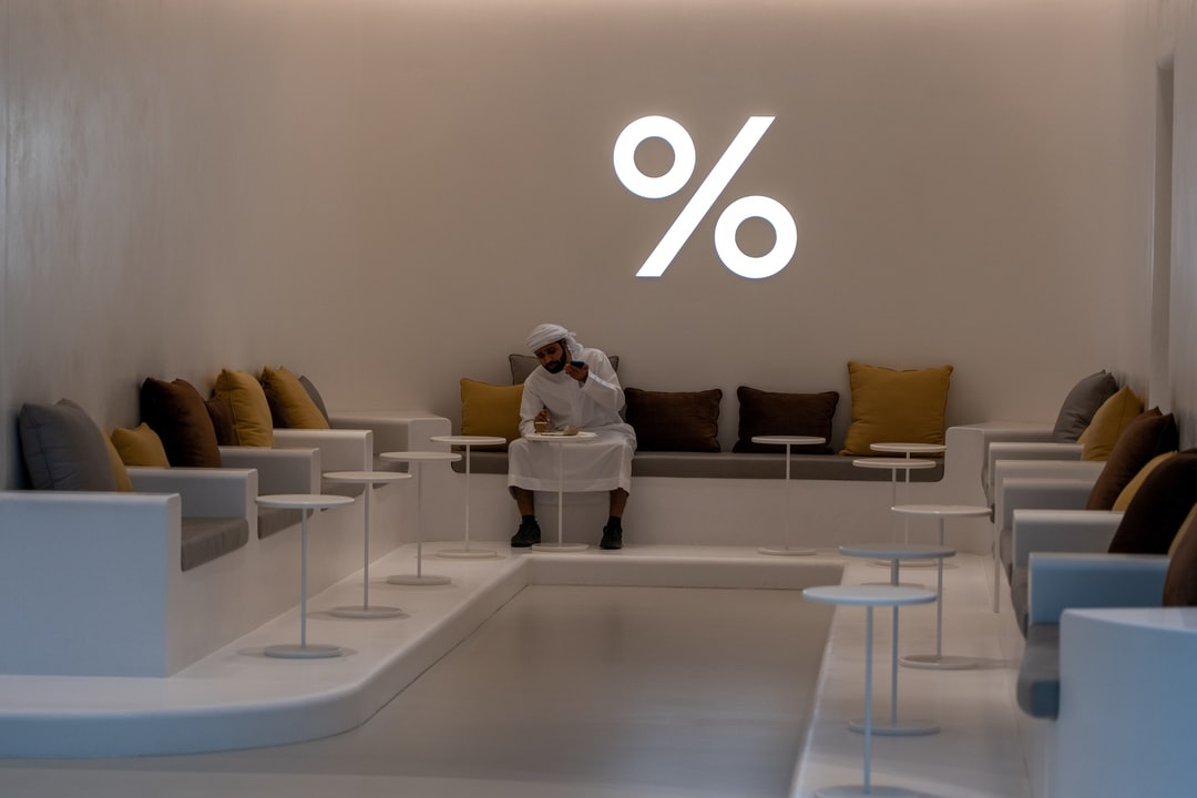 A man having a coffee in one of the coffee shops in the Dubai Mall, UAE.  I loved the white of his traditional outfit, against the white of the floor, tables and percentage symbol.