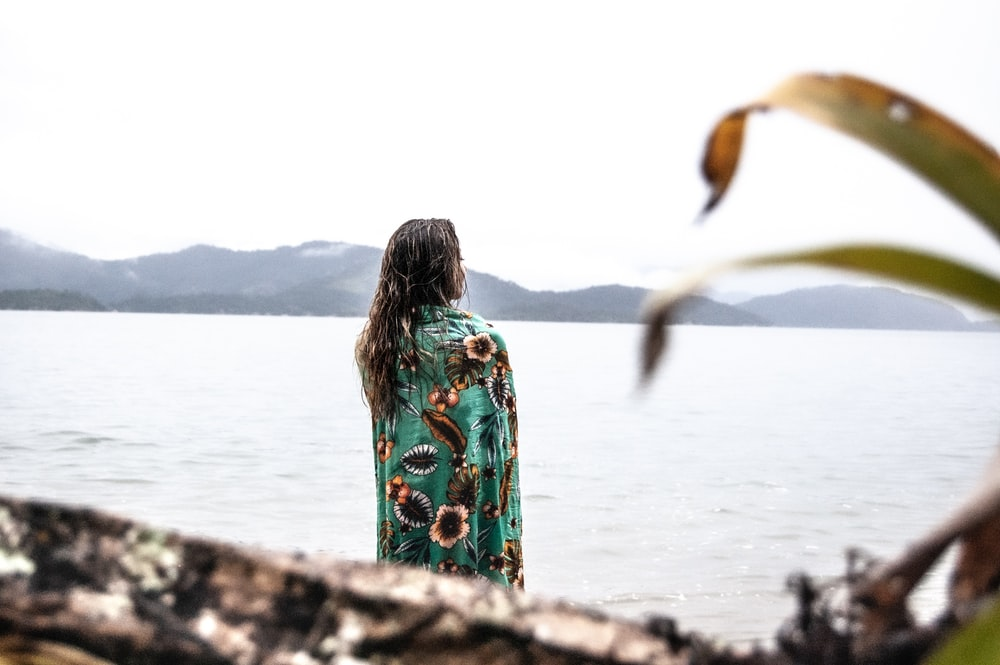 woman in green and white floral dress standing on rock near body of water during daytime
