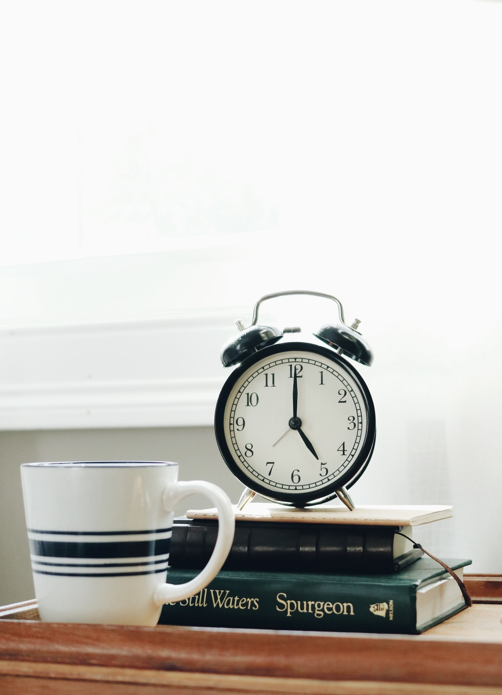 white ceramic mug beside white and black analog alarm clock