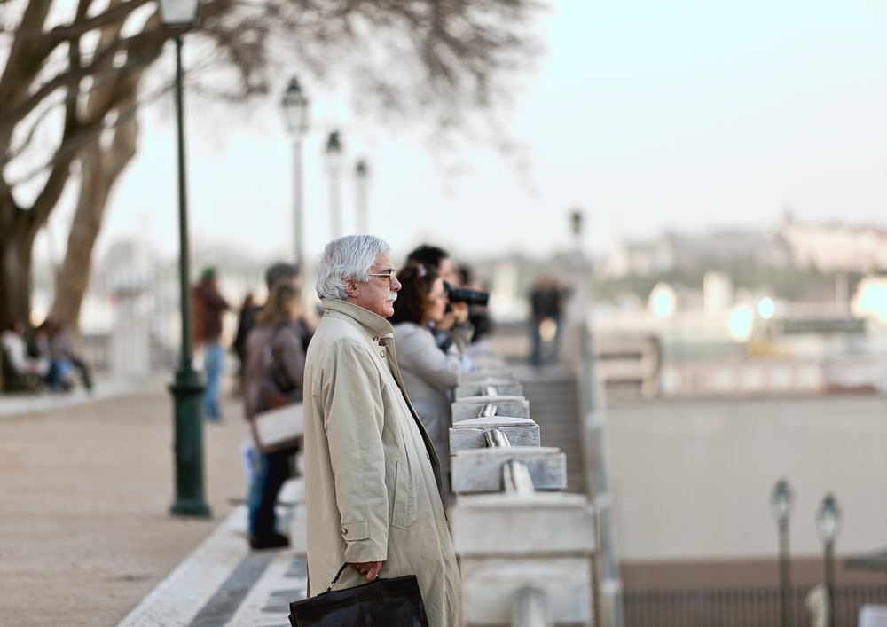 woman in beige coat walking on sidewalk during daytime