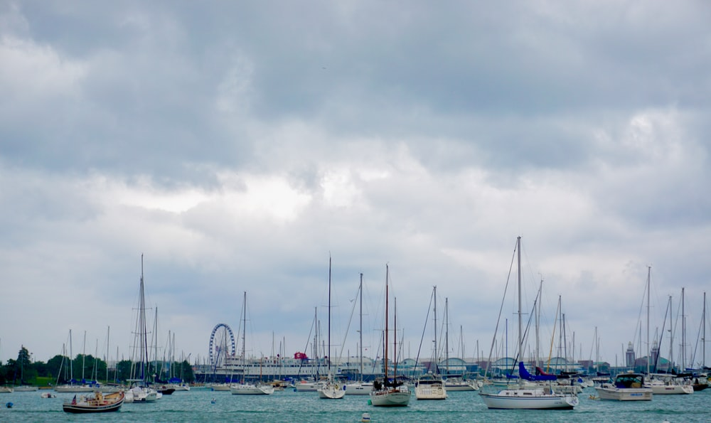 white and blue boats on sea under gray sky