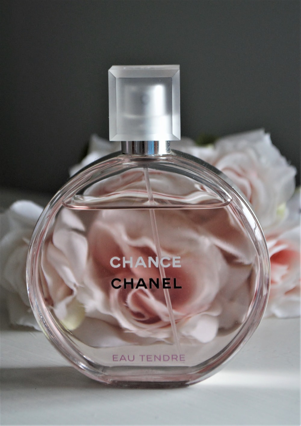 clear glass perfume bottle with pink liquid