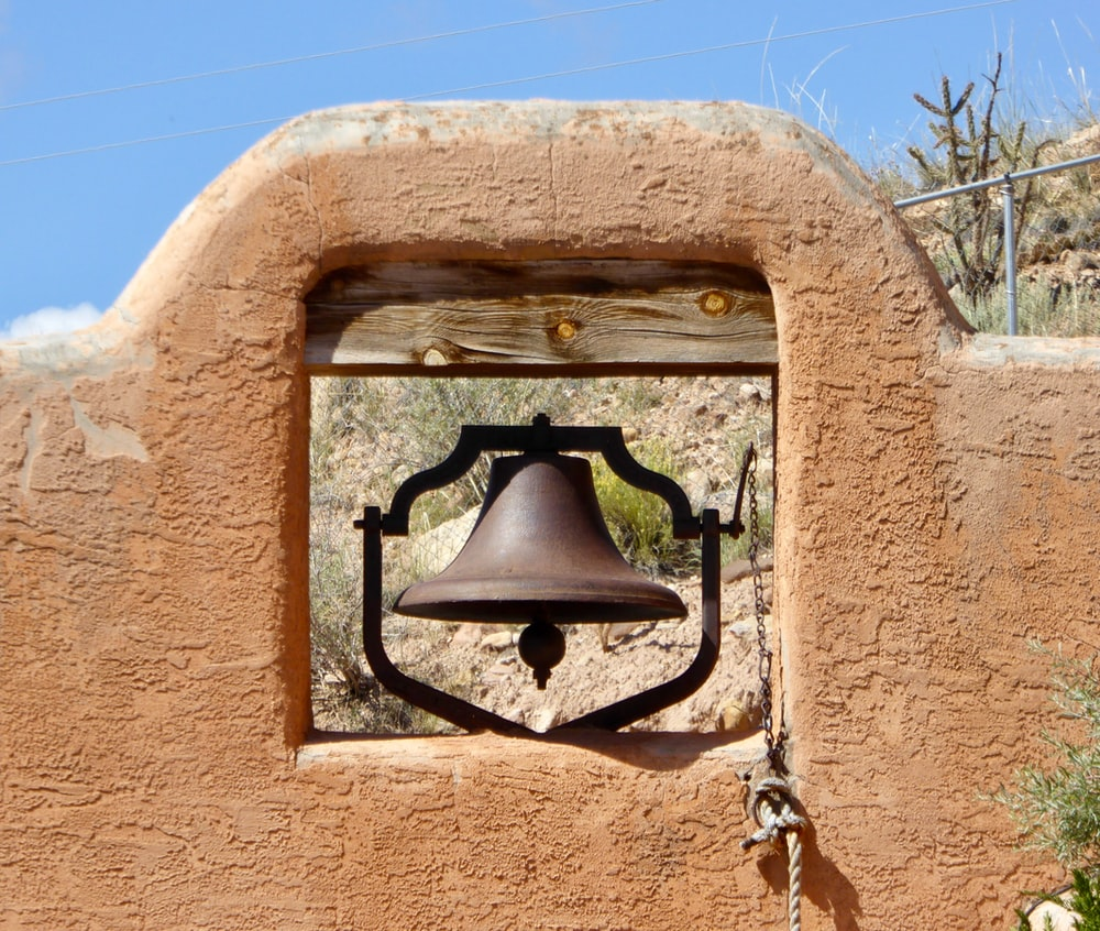 black bell on brown concrete wall
