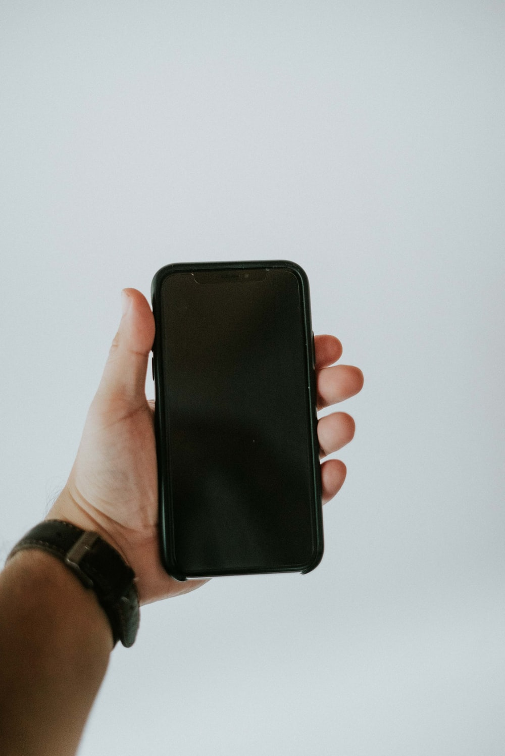 person holding black iphone 5 c
