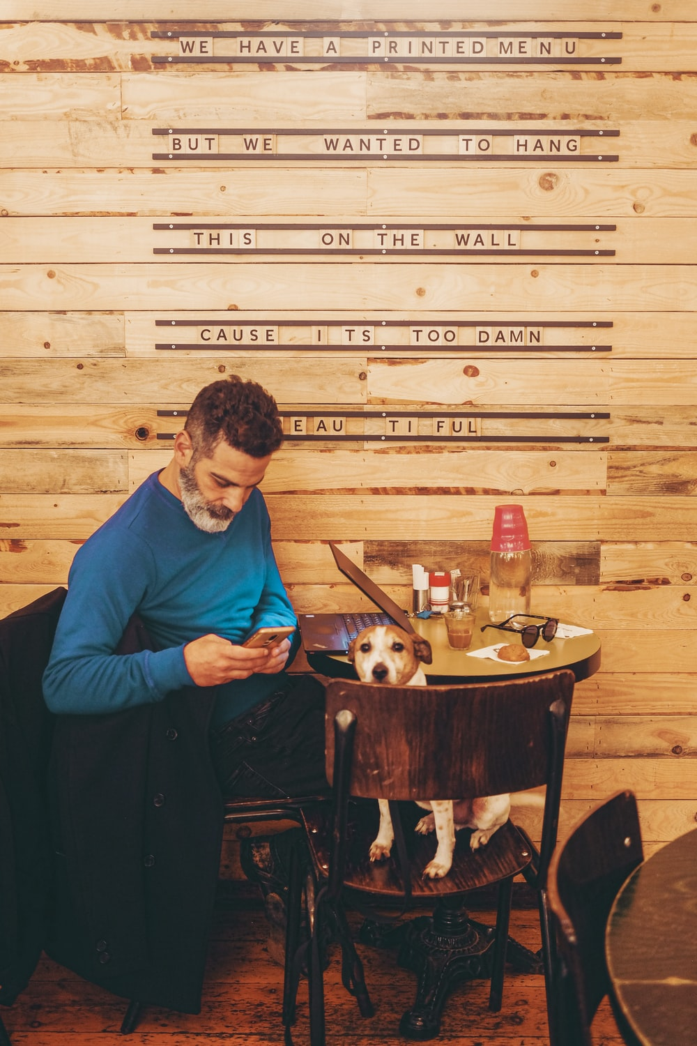 man in blue long sleeve shirt sitting on brown wooden seat