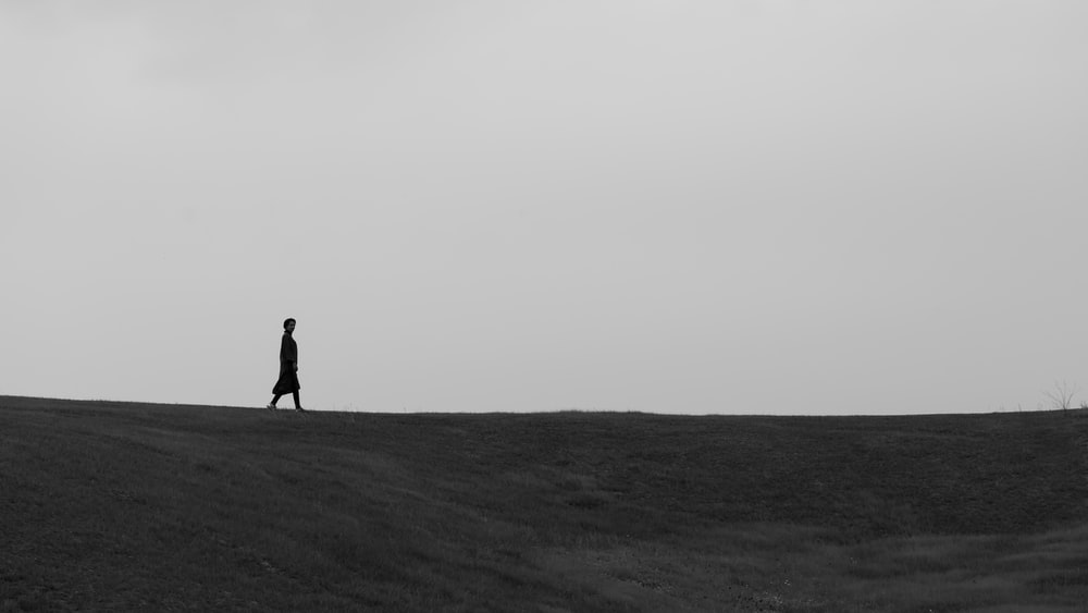 silhouette of person walking on field during daytime