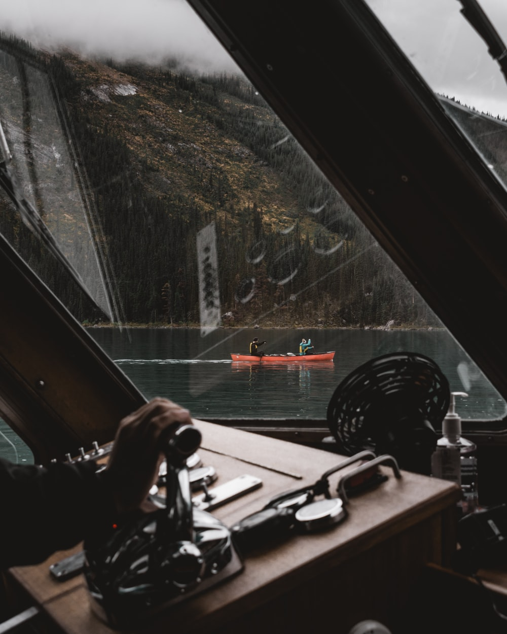 person holding black dslr camera on brown wooden boat during daytime