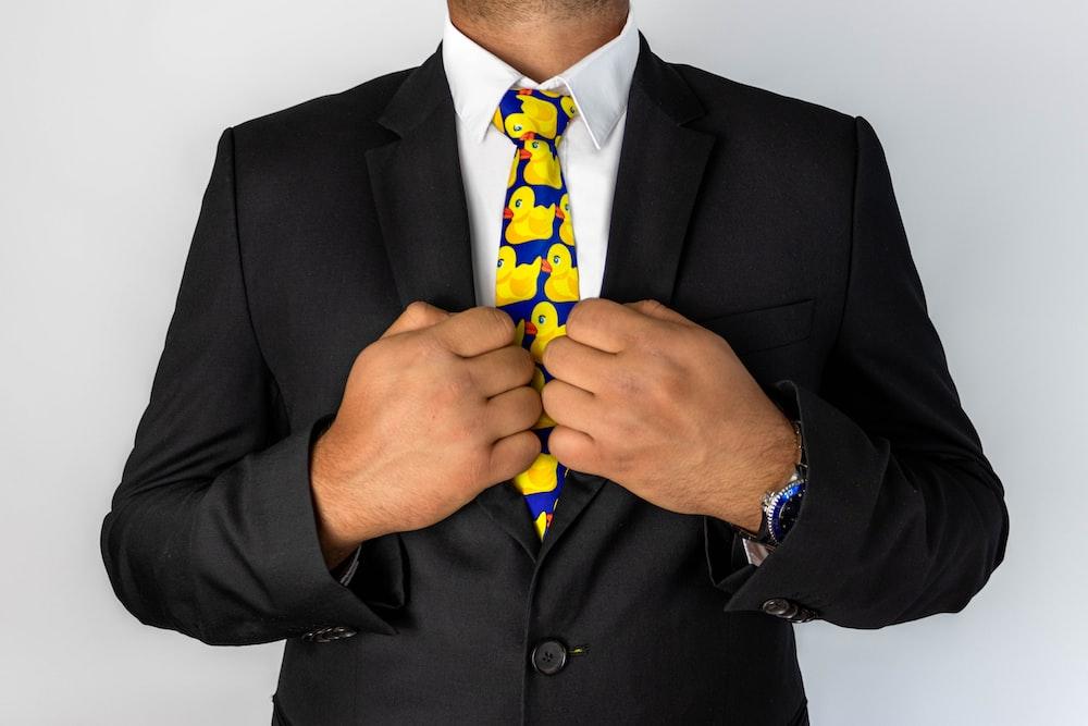 man in black suit jacket with blue necktie