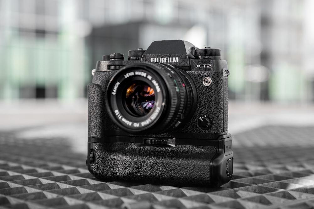 black nikon dslr camera on black and white checkered textile