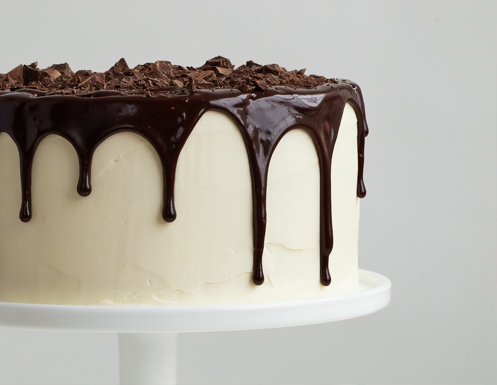 white cake with chocolate syrup on white ceramic plate