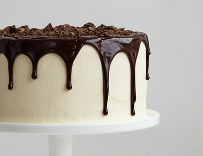 white cake with chocolate syrup on white ceramic plate cake zoom background