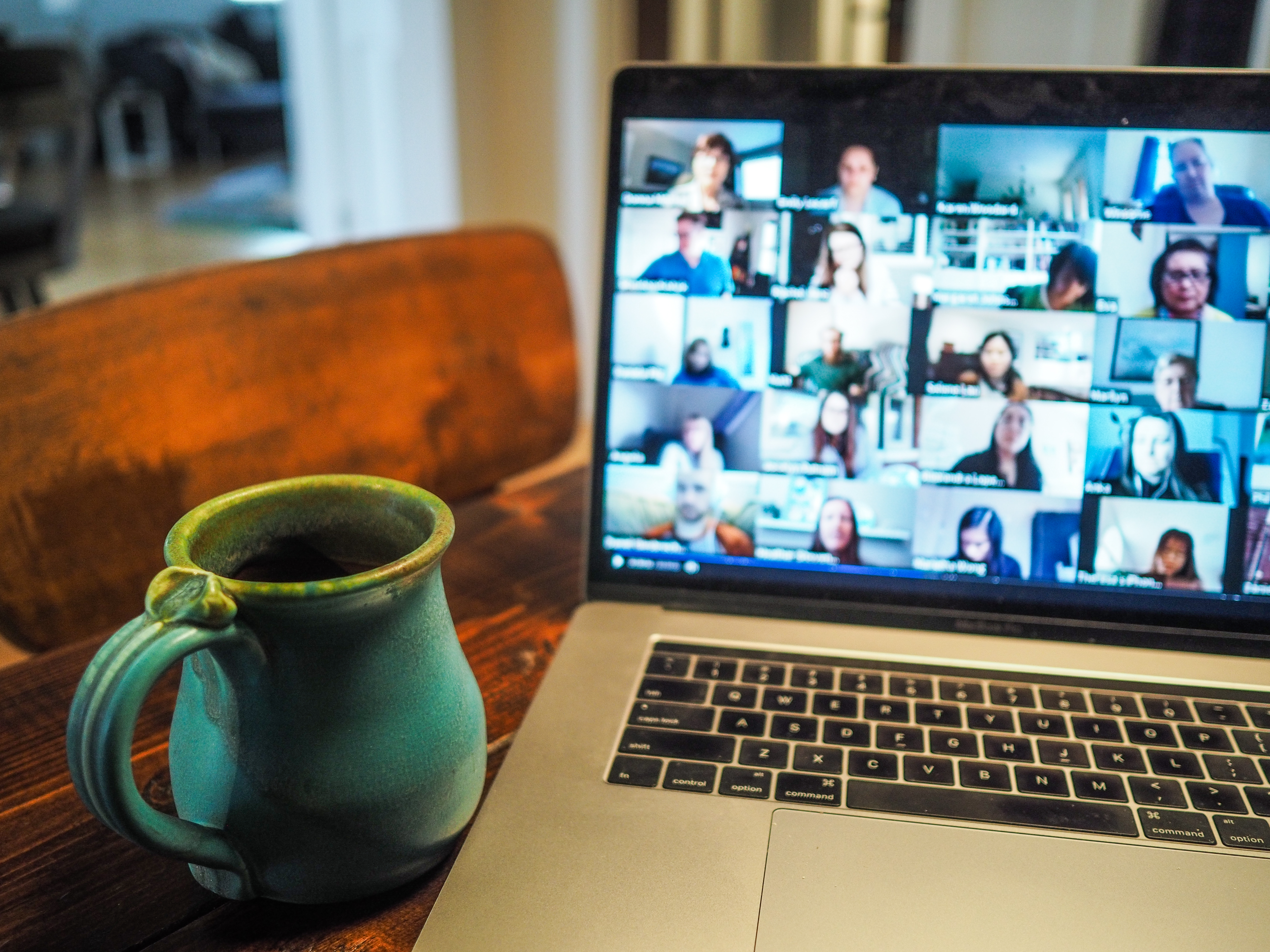 Coffee mug next to a laptop featuring numerous attendees in an online meeting