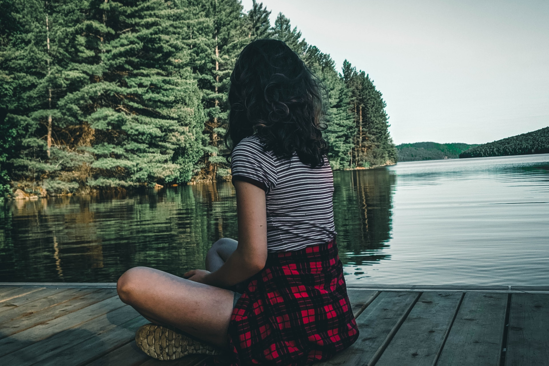 woman in black and white striped shirt sitting on dock during daytime