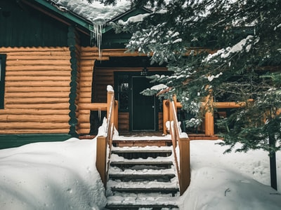 brown wooden staircase covered with snow log cabin zoom background