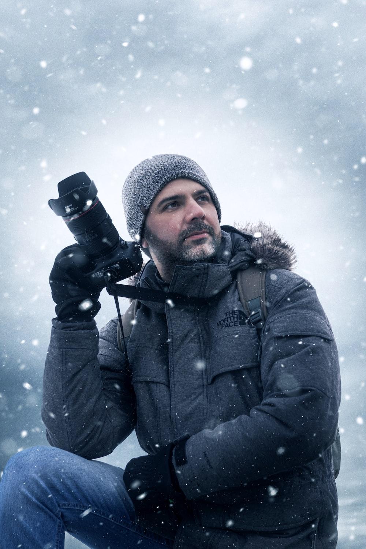 man in black jacket and knit cap holding black dslr camera