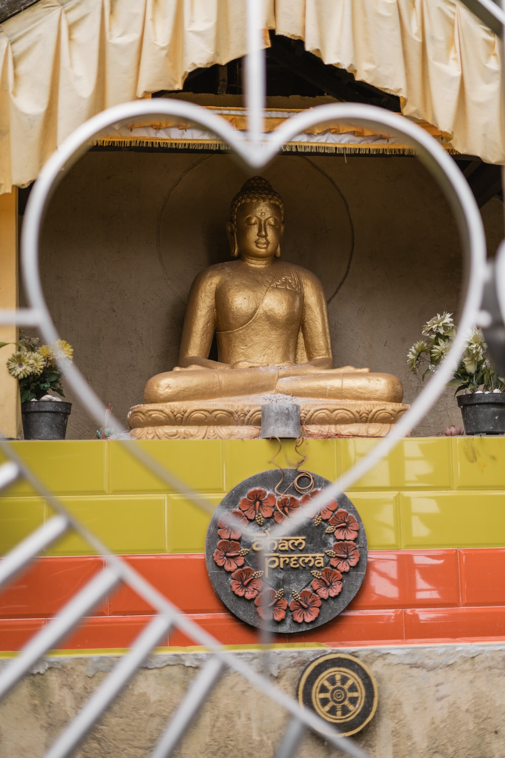 gold buddha statue with red and white round frame