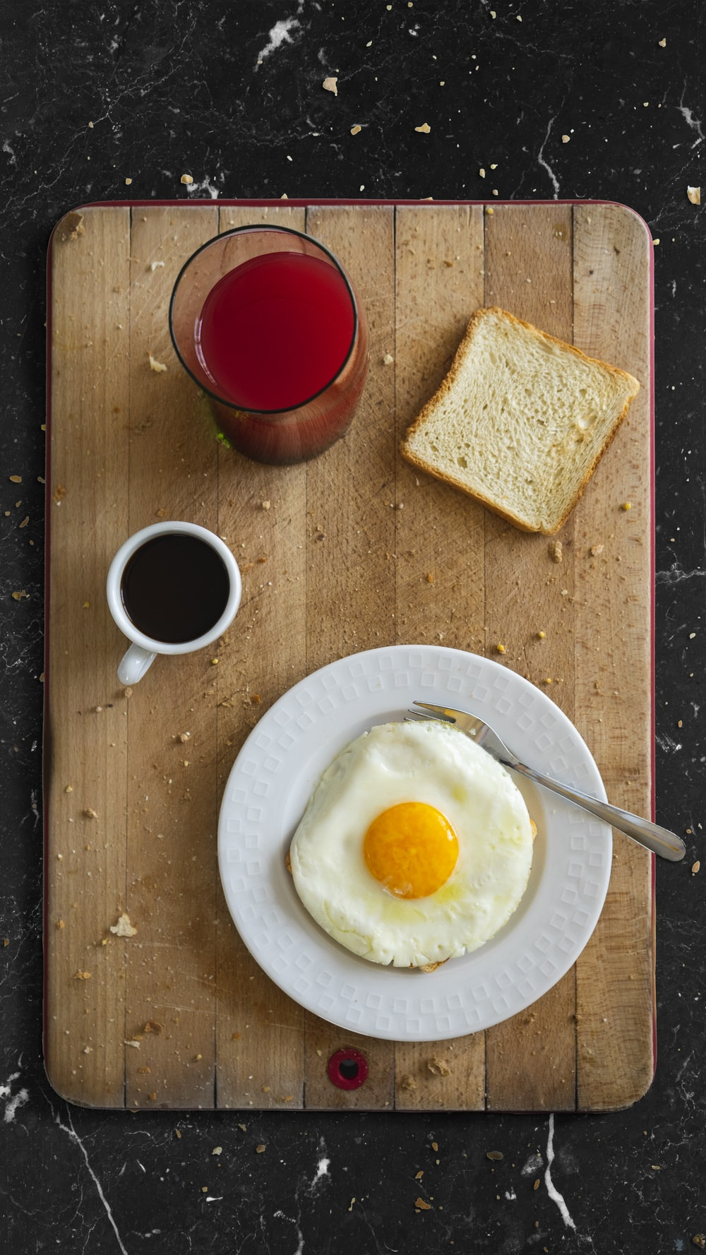 egg on white ceramic round plate beside red liquid in clear drinking glass