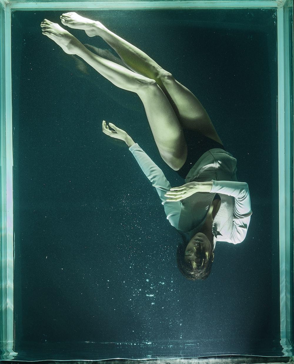 woman in white and black bikini lying on blue water