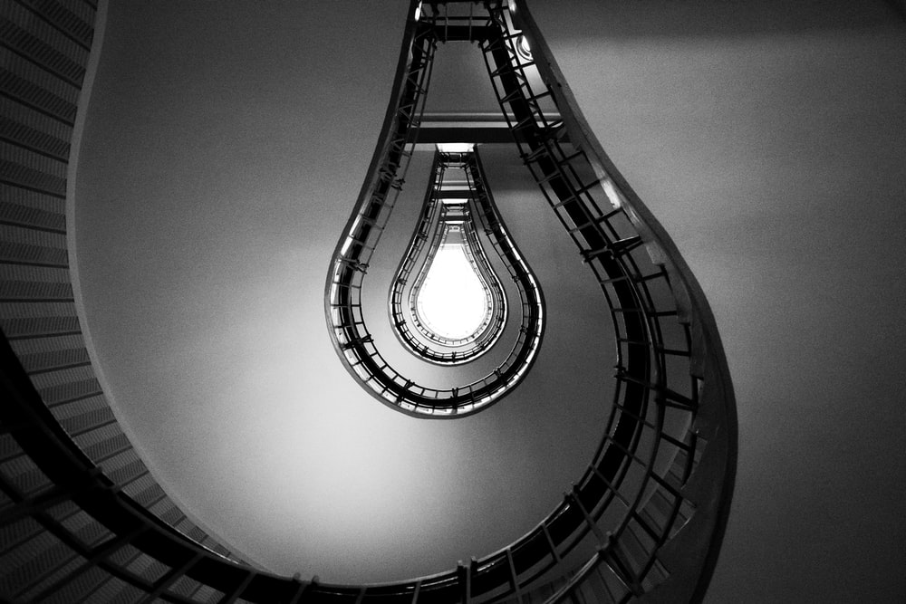 spiral staircase in grayscale photography
