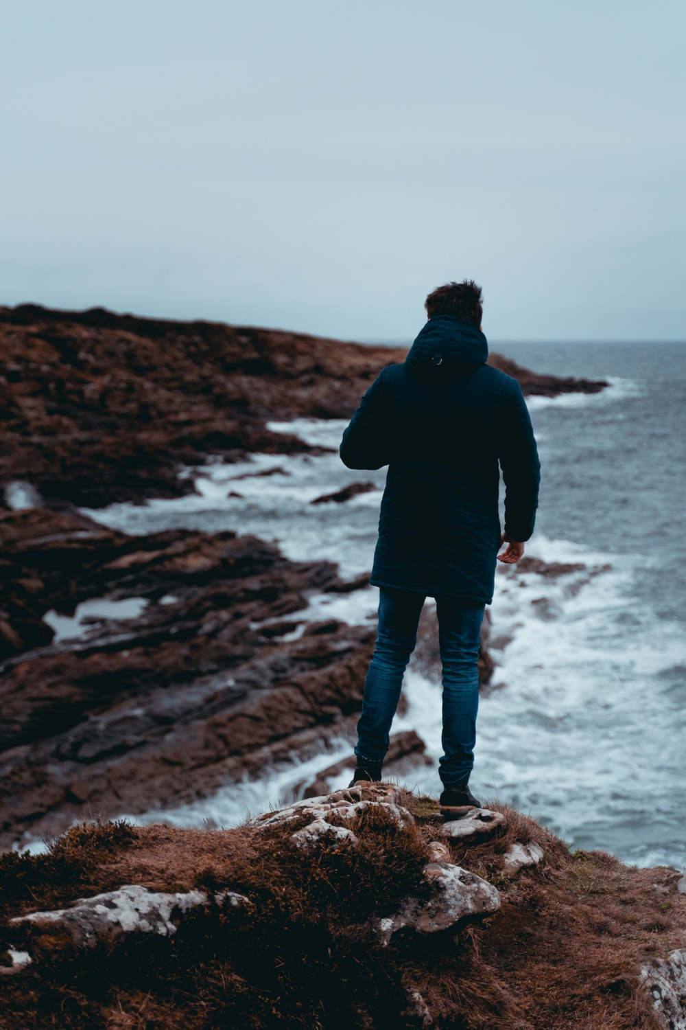man in black jacket standing on rock formation near sea during daytime