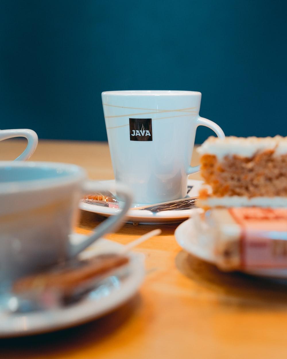 white ceramic mug on white ceramic saucer beside bread on white ceramic plate